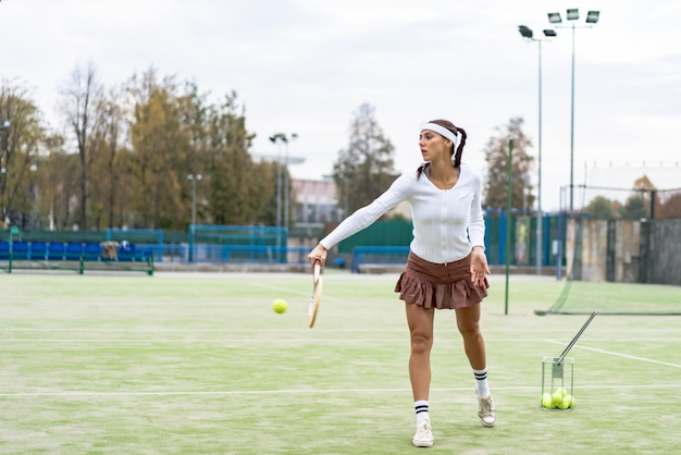 Portrait de belle femme jouant au tennis en plein air Photo gratuit