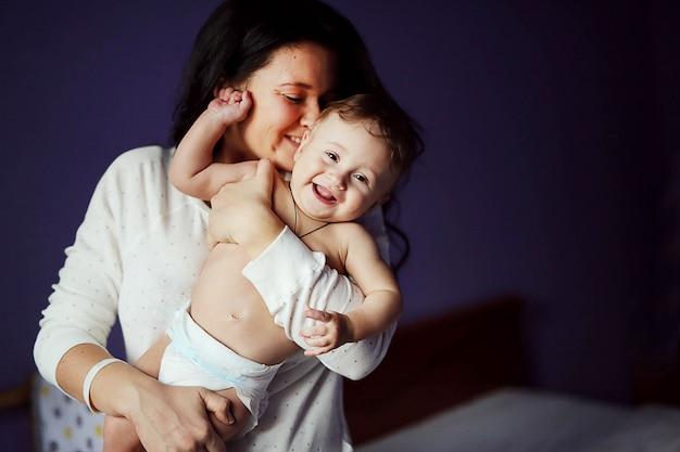 Portrait de belle femme joyeuse avec son bébé mignon s'amuser ensemble à la maison. doux garçon nu et mère brune. Photo Premium