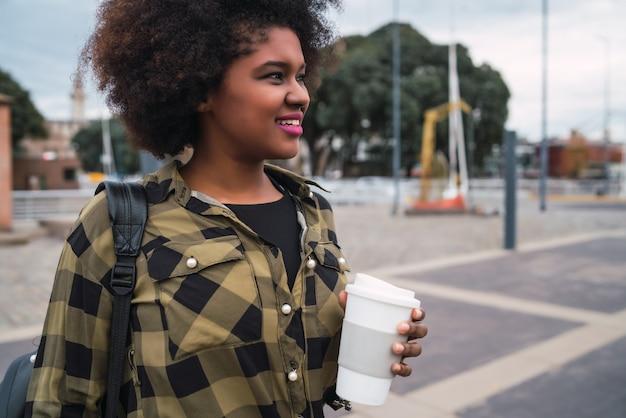 Portrait De La Belle Femme Latine Afro-américaine Tenant Une Tasse De Café à L'extérieur Dans La Rue. Concept Urbain. Photo gratuit