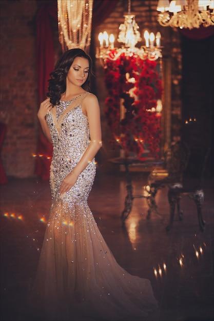 Portrait de belle femme en lumières sur un décor de noël. mode longue robe et makeup. Photo Premium