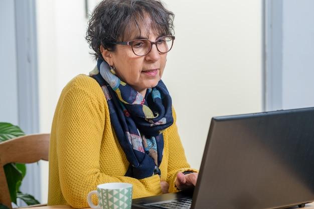 Portrait de belle femme mature brune avec un ordinateur portable à la maison Photo Premium