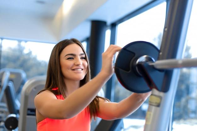 Portrait de la belle femme met la plaque de poids sur la barre dans la salle de gym Photo Premium