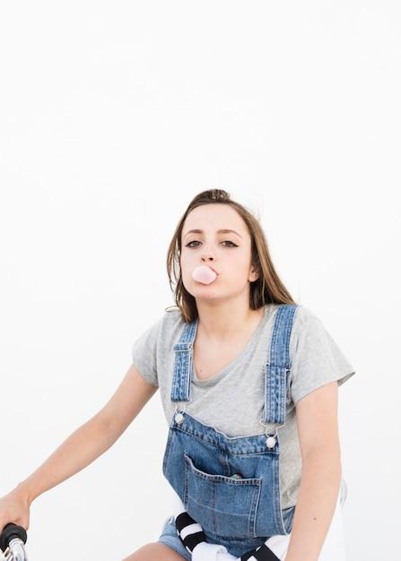 Portrait d'une belle femme soufflant du bubble-gum sur fond blanc Photo gratuit