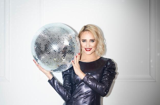Portrait De La Belle Femme Tenant Une Boule Disco Sur Un Mur Blanc Photo gratuit