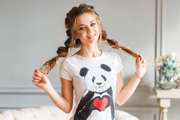 Portrait de belle fille aux yeux bruns et cheveux en queue de cochon souriant Photo gratuit