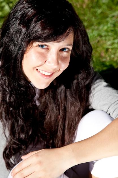 Portrait de belle fille brune aux yeux bleus sur l'herbe verte dans le parc. Photo Premium