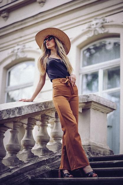 Portrait de belle fille cool gesticulant en chapeau et des lunettes de soleil sur le mur de grunge Photo Premium