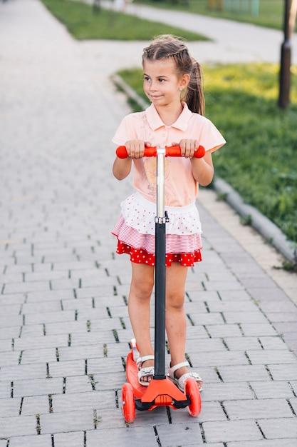 Portrait de belle fille debout sur le trottinette dans le parc Photo gratuit