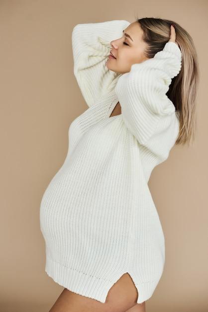 Un portrait de belle fille enceinte vêtu d'un pull blanc sur fond beige. Photo Premium