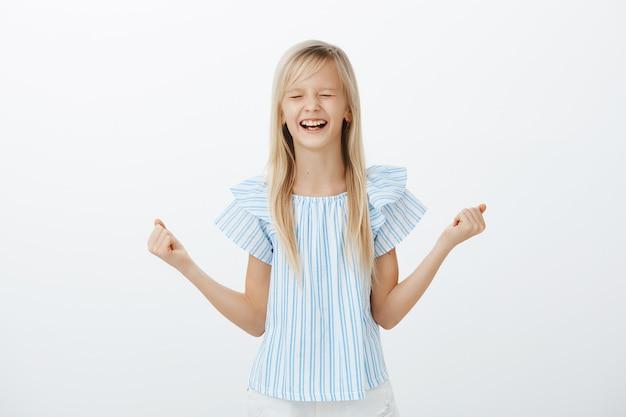 Portrait De Belle Fille Heureuse Et Excitée Aux Cheveux Blonds En Chemisier Bleu, Serrant Le Poing Levé, Fermant Les Yeux Et Hurlant De Joie Et De Bonheur, étant Joyeux, Gagnant La Première Place De L'événement Photo gratuit
