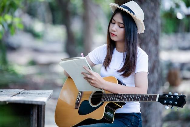 Portrait de belle fille jouant de la guitare avec l'écriture à la nature Photo gratuit