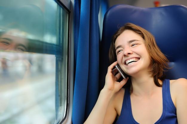 Portrait d'une belle fille parlant au téléphone dans un wagon de train Photo Premium