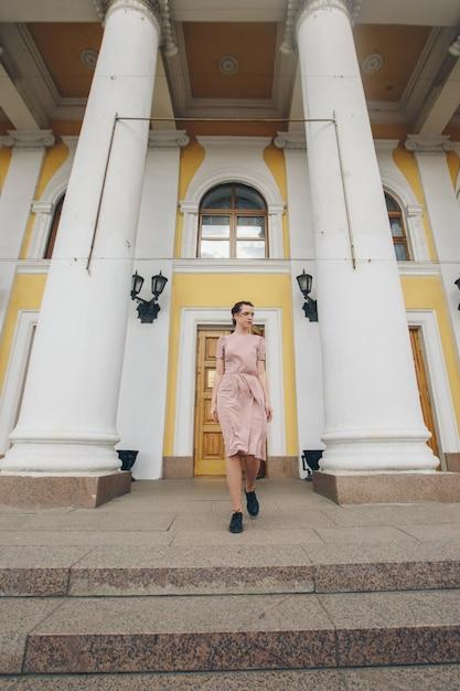 Portrait d'une belle fille près des colonnes du théâtre ou du musée Photo Premium
