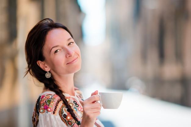 Portrait de belle fille avec une tasse de café dans la rue. caucasien touristique profiter de ses vacances en europe dans la ville vide Photo Premium
