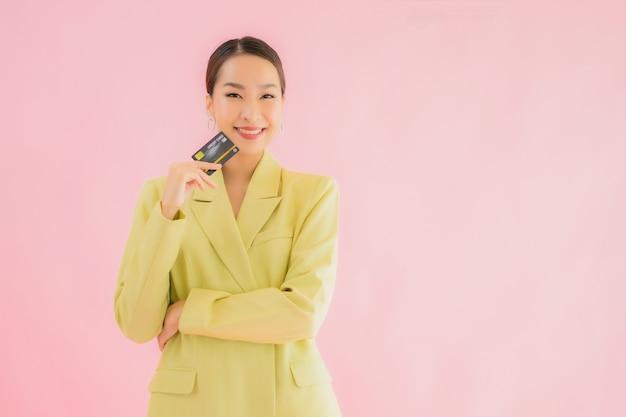 Portrait Belle Jeune Femme D'affaires Asiatique Avec Carte De Crédit Sur La Couleur Photo gratuit