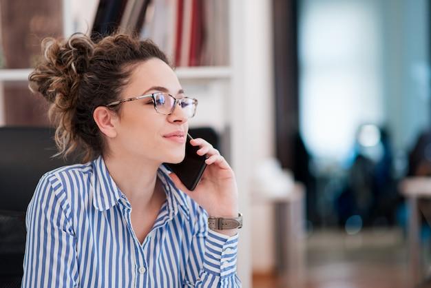 Portrait de la belle jeune femme d'affaires avec des lunettes, assis sur le lieu de travail et parler au téléphone mobile Photo Premium