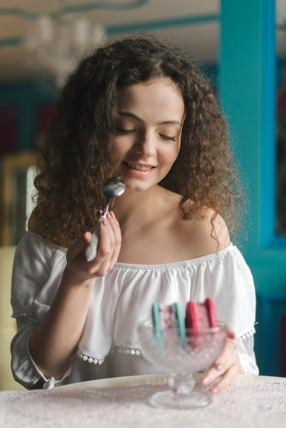Portrait de la belle jeune femme appréciant le sandwich à la crème glacée Photo gratuit
