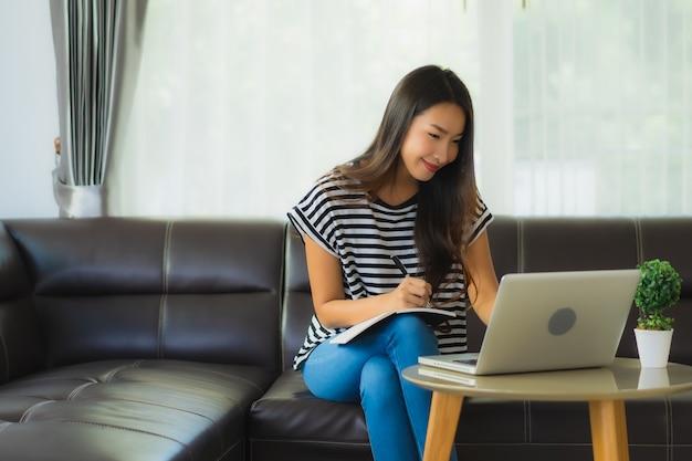 Portrait De La Belle Jeune Femme Asiatique à L'aide D'un Ordinateur Portable Sur Le Canapé Photo gratuit