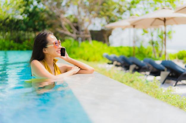Portrait belle jeune femme asiatique à l'aide de téléphone portable ou téléphone portable dans la piscine Photo gratuit