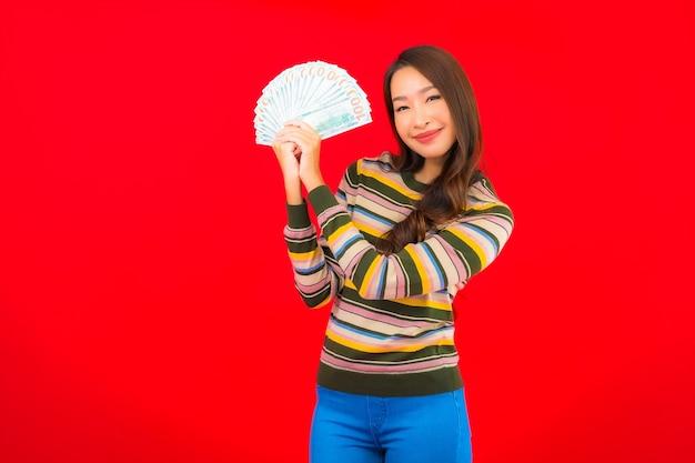 Portrait Belle Jeune Femme Asiatique Avec De L'argent Comptant Et Téléphone Mobile Sur Mur Rouge Photo gratuit