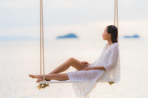 Portrait belle jeune femme asiatique assise sur la balançoire autour de la mer, mer, océan pour se détendre Photo gratuit
