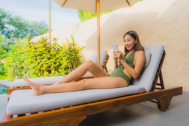 Portrait belle jeune femme asiatique assise sur le pont de la chaise avec piscine près de parasol Photo gratuit