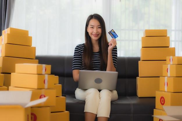 Portrait De La Belle Jeune Femme Asiatique Avec Des Boîtes De Colis En Carton Et Carte De Crédit Photo gratuit