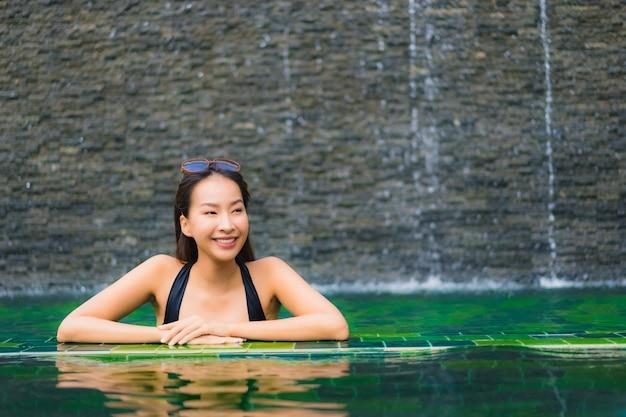 Portrait belle jeune femme asiatique dans la piscine autour de l'hôtel et la station Photo gratuit