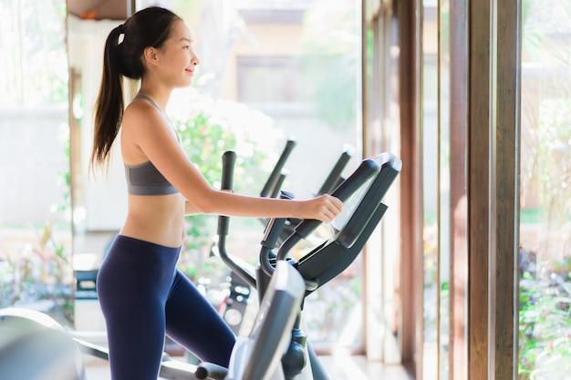Portrait belle jeune femme asiatique exercice avec appareils de fitness à l'intérieur de la salle de gym Photo gratuit