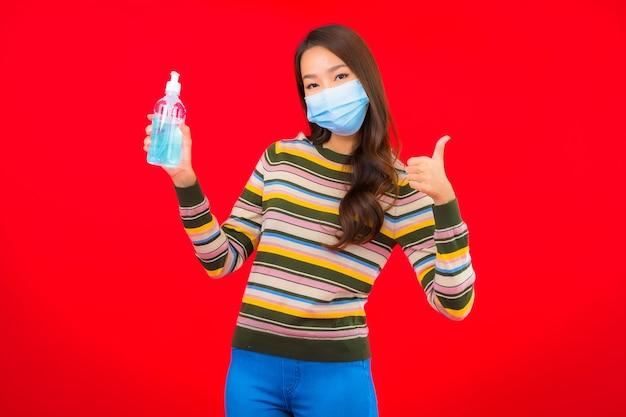 Portrait Belle Jeune Femme Asiatique Avec Gel D'alcool Sur Mur Isolé Rouge Photo gratuit