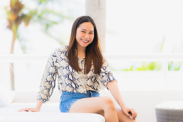 Portrait belle jeune femme asiatique heureuse et souriante avec voyage dans hôtel resort neary mer et plage Photo gratuit