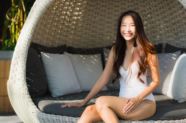 Portrait belle jeune femme asiatique heureuse sourire et se détendre autour de la piscine dans l'hôtel resort Photo gratuit