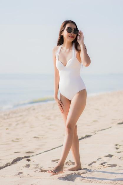 Portrait belle jeune femme asiatique heureuse et sourit sur la plage, la mer et l'océan Photo gratuit