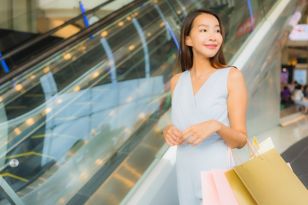 Portrait belle jeune femme asiatique heureuse et sourit avec sac à provisions du grand magasin Photo gratuit