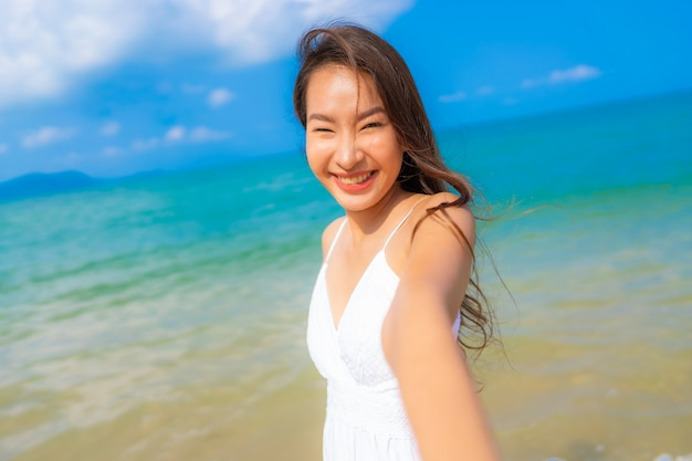 Portrait belle jeune femme asiatique heureux sourire loisirs sur la plage, mer et océan Photo gratuit