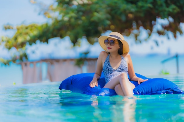 Portrait Belle Jeune Femme Asiatique Heureux Sourire Se Détendre Dans La Piscine De L'hôtel Resort Près De La Mer Océan Plage Sur Ciel Bleu Photo gratuit