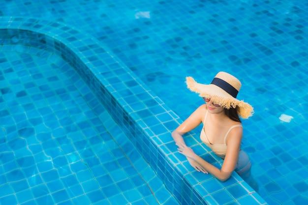 Portrait belle jeune femme asiatique heureux sourire se détendre piscine en plein air dans la station Photo gratuit