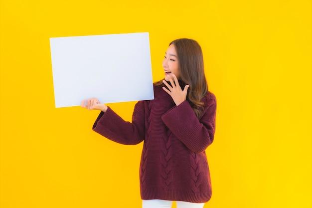 Portrait Belle Jeune Femme Asiatique Montrer Carton Blanc Vide Photo gratuit