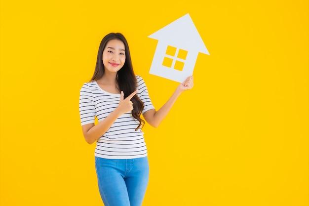 Portrait Belle Jeune Femme Asiatique Montrer Signe Maison Photo gratuit
