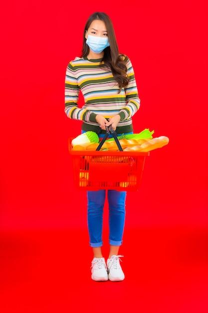 Portrait Belle Jeune Femme Asiatique Avec Panier D'épicerie De Supermarché Sur Mur Isolé Rouge Photo gratuit