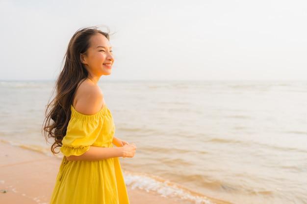 Portrait belle jeune femme asiatique à pied sur la plage et la mer Photo gratuit