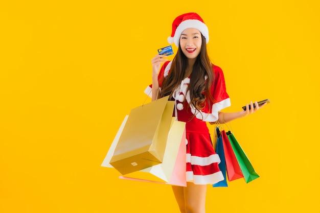 Portrait Belle Jeune Femme Asiatique Porter Des Vêtements De Noël Chapeau Avec Beaucoup De Sac à Provisions Photo gratuit