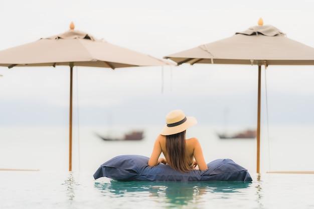 Portrait belle jeune femme asiatique se détendre dans la piscine extérieure de luxe dans l'hôtel resort près de la mer Photo gratuit
