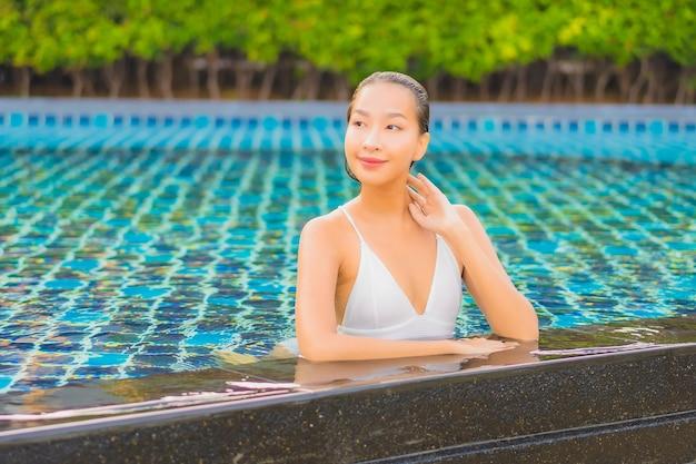 Portrait Belle Jeune Femme Asiatique Se Détendre Sourire Loisirs Autour De La Piscine Extérieure Près De La Mer Photo gratuit