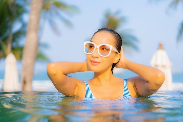 Portrait Belle Jeune Femme Asiatique Se Détendre Sourire Profiter De Loisirs Autour De La Piscine Près De La Mer Plage Vue Sur L'océan En Vacances Photo gratuit