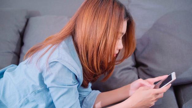 Portrait de la belle jeune femme asiatique souriante attrayante à l'aide de smartphone en position couchée sur le canapé Photo gratuit