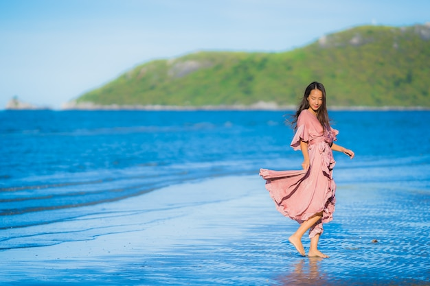 Portrait belle jeune femme asiatique sourire promenade heureuse sur la mer tropicale en plein air nature plage Photo gratuit
