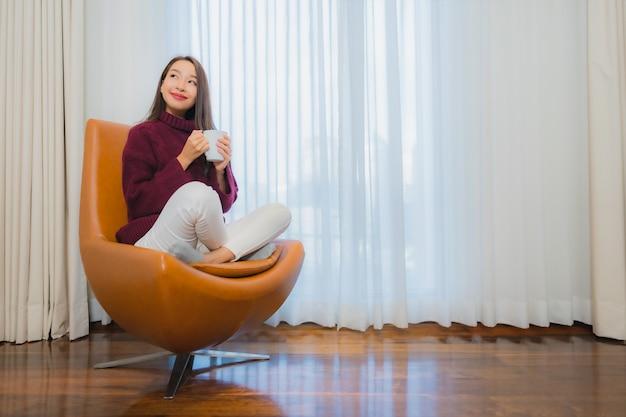 Portrait Belle Jeune Femme Asiatique Sourire Se Détendre Sur Le Canapé à L'intérieur Du Salon Photo gratuit