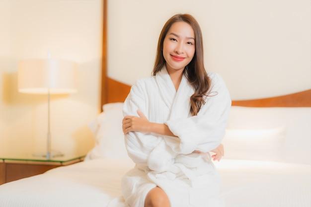 Portrait Belle Jeune Femme Asiatique Sourit Reposant Sur Le Lit à L'intérieur De La Chambre Photo gratuit