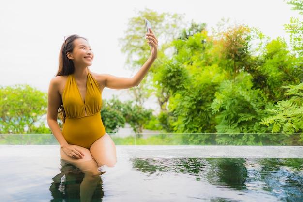 Portrait belle jeune femme asiatique avec téléphone portable ou téléphone portable autour de la piscine de l'hôtel Photo gratuit